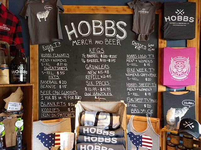 Hobbs Tavern merch, including shirts, growlers, six packs, kegs, and koozies
