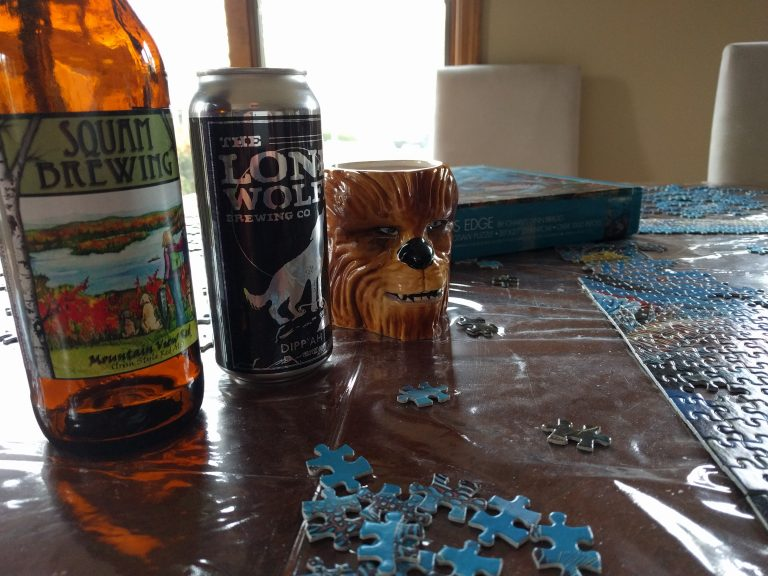 Squam Brewing and Lone Wolfe Brewing Company aid in finishing a puzzle.